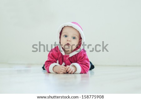 Small boy in Santa suit plays in white studio