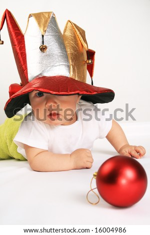 Small boy in the hat of jester plays with the red sphere