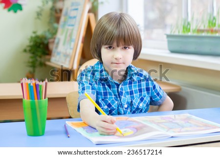 Small boy is coloring copybook in class