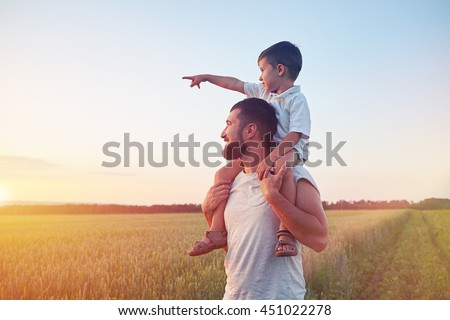 Small boy is sitting on his father??s shoulders and pointing at the sun in the field during beautiful sunset  - stock photo