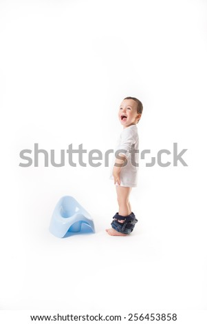 Small boy is smiling next to the blue potty - stock photo