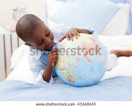 Small boy looking at a Globe in his bedroom - stock photo