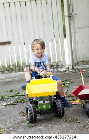 Small boy on his toys tractor