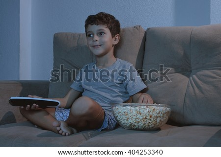 Small boy on the couch watching TV and eating popcorn at night in the living room - stock photo