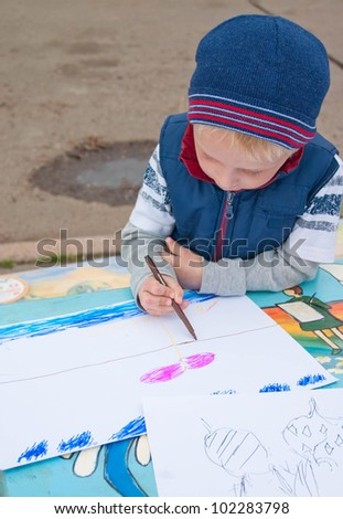 Small boy painting outdoors - stock photo
