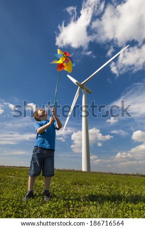 Small boy playing with a multicolored pinwheel near wind turbines - stock photo