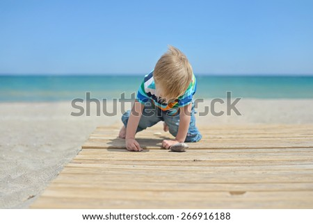 Small boy playing with stones on a wooden walkway on the beach - stock photo
