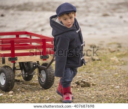 small boy pulling his big red wooden wagon across the rocky, sandy ocean beach. - stock photo