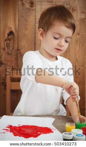 small boy sits at the table and play a brush and paints, draws on paper and on the hands