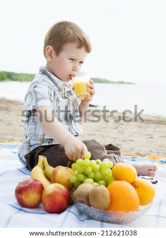 Small boy sitting near fruits and drinking juice at beach  - stock photo