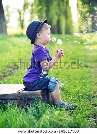 Small boy sitting on an old suitcase - stock photo