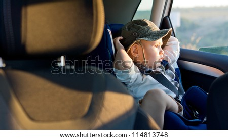 Small boy sitting strapped into a child seat in the rear of a car staring out of the window - stock photo