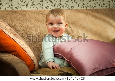 small boy smiling on the couch - stock photo