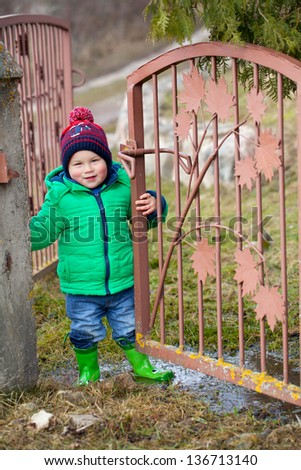 small boy  standing in puddle after the rain - stock photo