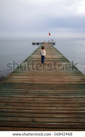 Small boy standing on a pier