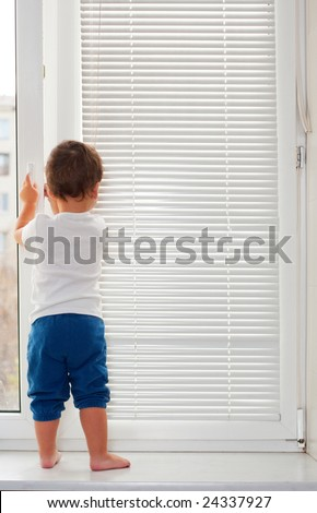 Small boy standing on white window-sill - stock photo