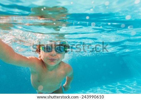 Small boy swimming wearing goggles under the crystal-clear water of swimming pool - underwater shoot