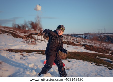 Small boy tossing a snowball at the camera as he plays outdoors in a snowy winter field