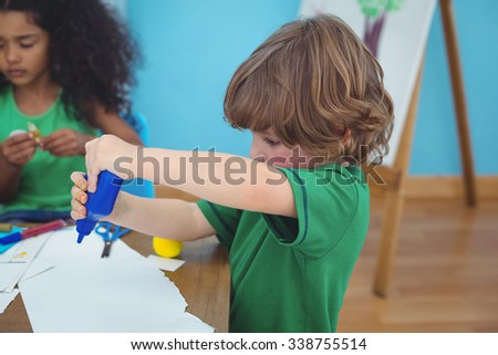 Small boy using arts and crafts supplies at their desk - stock photo