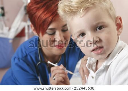 Small boy watching as nurse gives him a shot. - stock photo