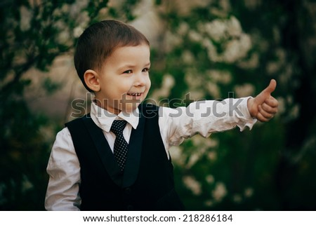 small boy wear suit smiling outdoor and feel happy - stock photo