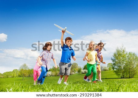 Small boy with airplane toy and friends running - stock photo