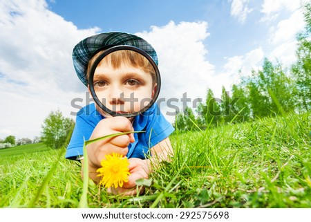 Small boy with magnifier and yellow flower - stock photo
