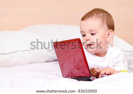small boy with red laptop at home