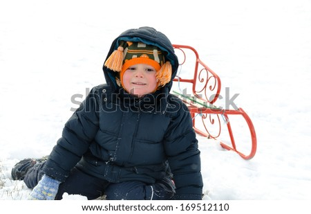 Small boy wrapped up warmly against the winter cold kneeling in the snow with a bright orange metal sled watching something with a serious expression - stock photo