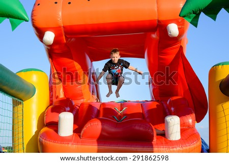 Small boy (6-8 years) wearing t-shirt and shorts jumping bare foot in the air on a colorful bouncy castle, blue sky in background - stock photo