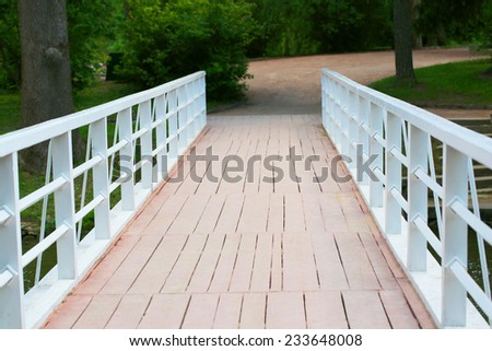 Small bridge in green park - stock photo