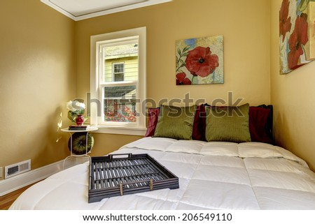 Small bright room with  windows and hardwood floor. View of bed with green and burgundy pillows - stock photo
