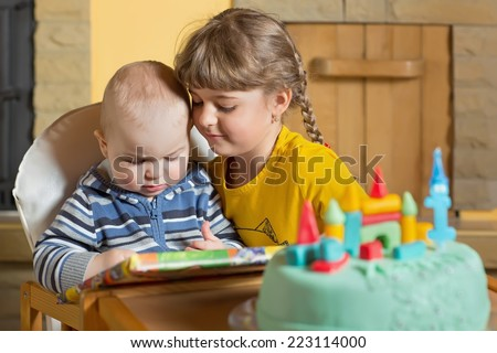 Small brother and older sister playing at home - stock photo