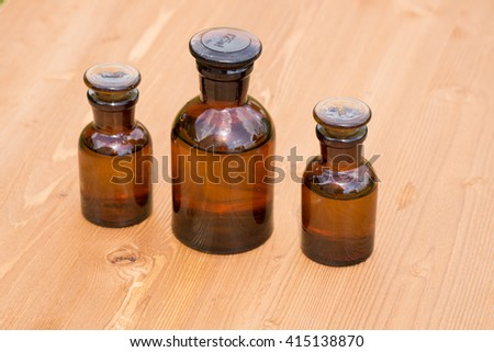 Small brown glass bottles on wooden board - stock photo