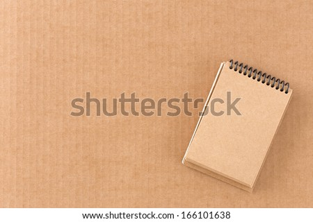 Small brown notebook on cardboard background - stock photo