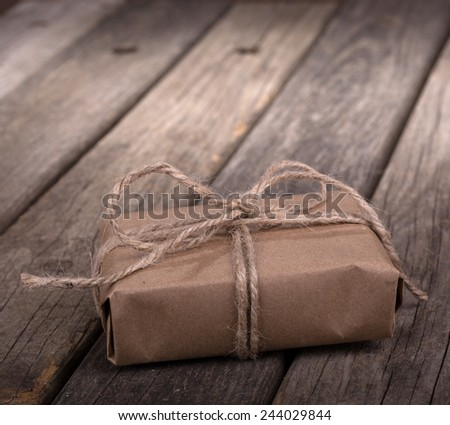 Small brown package wrapped with string on old wood boards - stock photo