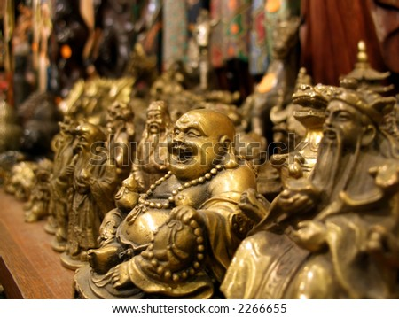 Small Buddha crafts lined on a shop bench, focus on the smiling one