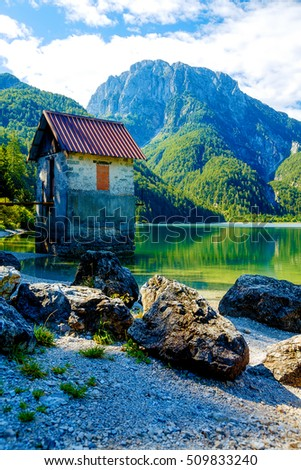 small building at a beautiful lake surrounded by stunning mountain landscape.
