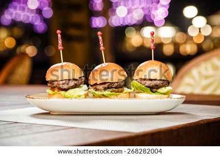 Small burgers served on one plate as appetizers  - stock photo
