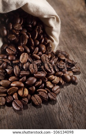 small burlap bag with coffee beans spilling out - stock photo