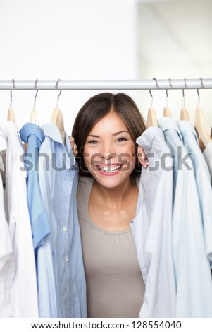 Small business clothing shop owner portrait in store. Funny image of woman clothes shop owner peeping through shirts smiling happy and excited at camera. Multicultural Asian Caucasian female model.