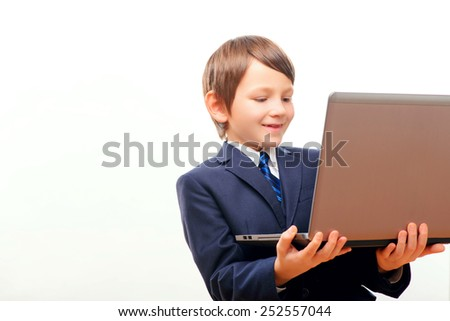 Small business. Cute little boy in tie and formalwear holding the laptop and smiling while standing against white background with copy space - stock photo
