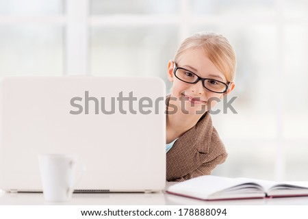 Small business. Cute little girl in glasses and formalwear looking out of the laptop and smiling while sitting at the table  - stock photo