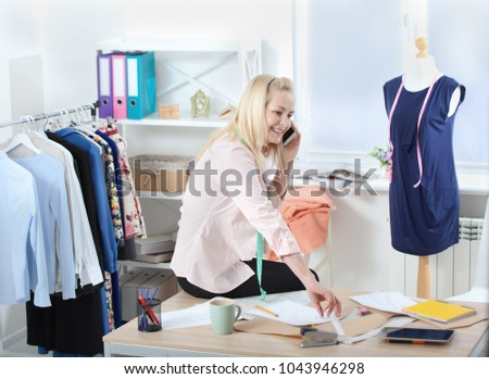 Small business enterprise concept. Communication with suppliers by phone, skype. Woman tailor talking on the phone, standing near the table in the workshop with clothes hanging in the background.
