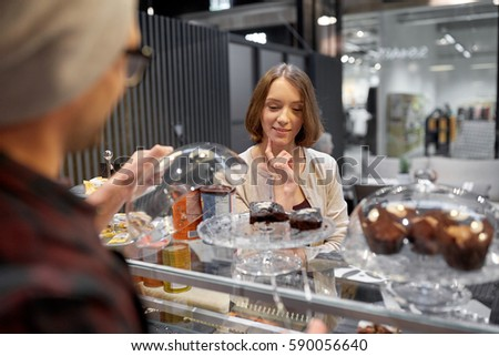 small business, food, people and service concept - happy woman choosing cakes at vegan cafe or coffee shop