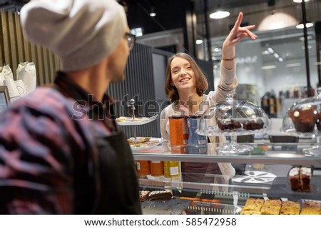 small business, food, people and service concept - happy woman showing something to seller or bartender at vegan cafe