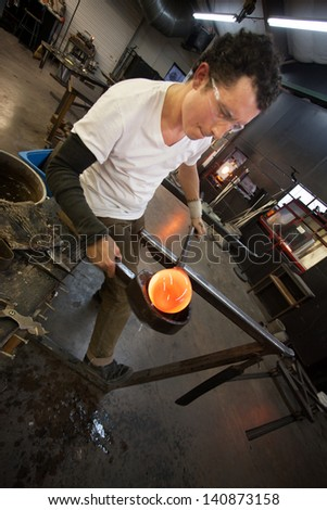 Small business glass manufacturer forming glowing hot object - stock photo