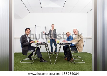 Small business meeting, with four people in a small stylish conference room with grass on the floor, discussing strategy, growth, sustainability and environmental inpact of business, - stock photo