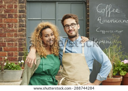 Small business owners standing in front of cafe wearing aprons portrait cafe ready for work - stock photo