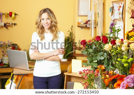 Small business. Portrait of friendly small flower shop owner standing in front of counter. Looking at camera and smiling.  - stock photo